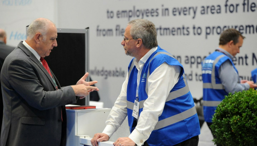 2 men, blue high-vis jackets, in discussion at exhibition